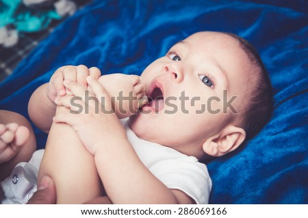 Close up portrait of cute baby boy lying on a blanket sucking his toes - stock photo