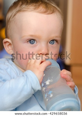 Close-up portrait of cute baby boy sitting and holding bottle with milk and drinking by himself.  Toddler has blue eyes, blue bottle and blue shirt. Child concept. - stock photo