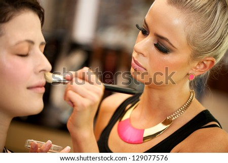 Close up portrait of cute blond make up artist applying color on face. - stock photo