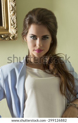 close-up portrait of cute brunette female with long wavy hair, stylish make-up and casual modern jacket. Looking in camera with happy expression  - stock photo
