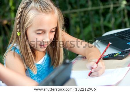 Close up portrait of cute girl doing homework in garden. - stock photo