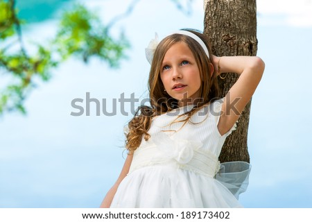 Close up portrait of cute girl in white dress against tree. - stock photo