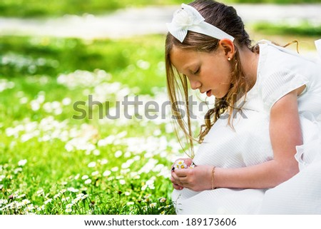 Close up portrait of cute girl in white dress picking flowers. - stock photo