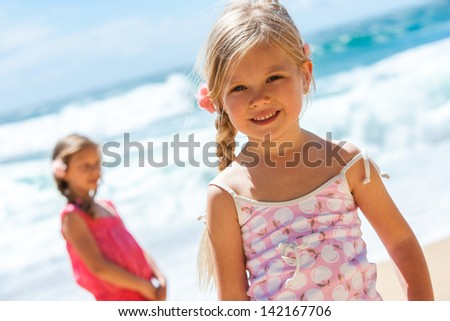 Close up portrait of cute girl on beach with friend in background. - stock photo