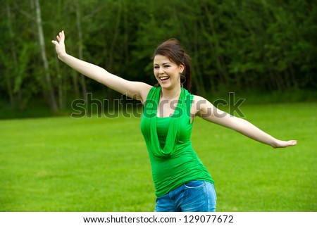 Close up portrait of cute girl with arms open in green park. - stock photo