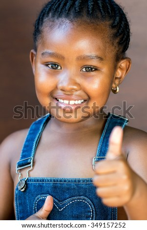 Close up portrait of Cute little african girl against dark brown background doing a thumbs up sign with thumb.