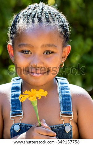 Close up portrait of cute little african girl with braided hairstyle holding orange flower outdoors. - stock photo