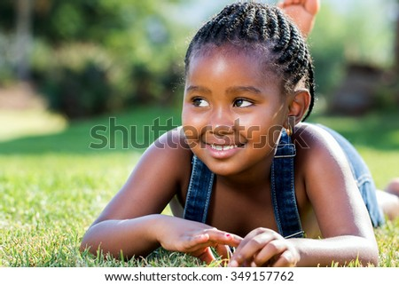 Close up portrait of cute little african girl with braids laying on green grass. - stock photo