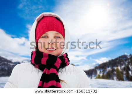 Close up portrait of cute smiling Caucasian girl in white coat on sunny winter day - stock photo