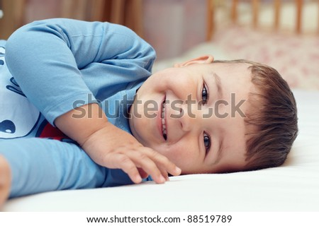 close-up portrait of cute smiling  little boy in blue shirt lying in bed - stock photo