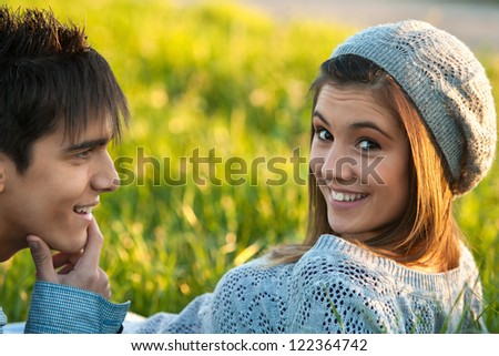 Close up portrait of cute teen girl and boyfriend laying in green grass field. - stock photo