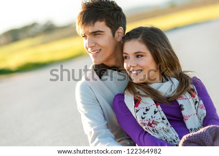 Close up portrait of cute young couple sitting together outdoors. - stock photo