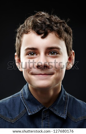 Close-up portrait of dimpled young boy isolated on black background - stock photo