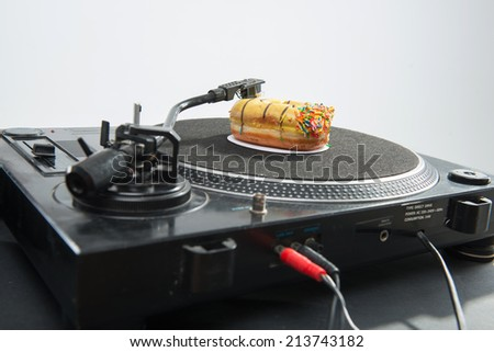 Close-up portrait of donut placed on vinyl record and turntable, isolated on white background - stock photo
