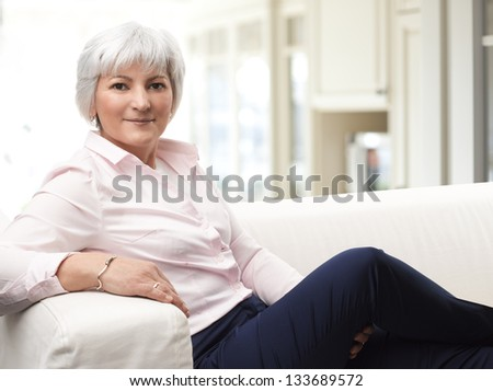Close-up portrait of elegant senior woman sitting in living room. - stock photo