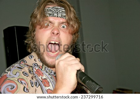 close-up portrait of emotional man singing a rock - stock photo