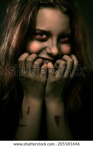 Close up portrait of evil scary girl possessed by a demon with a sinister smile - stock photo