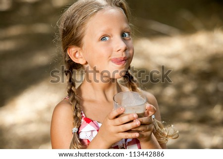 Close up portrait of expressive girl drinking chocolate milkshake.
