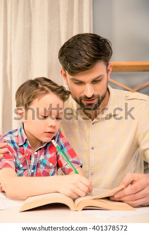 Close up portrait of father and son doing home task - stock photo