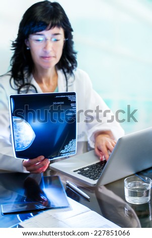 Close up portrait of Female doctor analyzing x-ray mammogram at desk in clinic. - stock photo