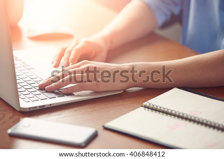 Close-up portrait of female hands keyboarding on the computer during sunny day in the office. Cropped view of successful businesswoman keyboarding on laptop. Flare sun, selective focus, film effect - stock photo