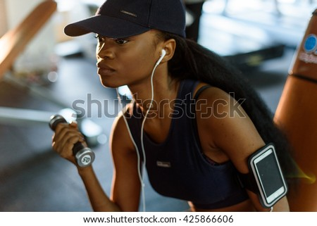 Close-up portrait of fitness instructor african american woman working out with dumbbells at the gym and listens music in earphones - stock photo