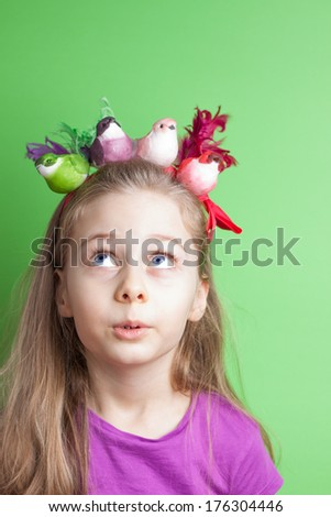 Close up portrait of five years old blond caucasian child girl looking up on colorful birds - pastel green background. Careless childhood and spring concept - layout with free text space. - stock photo