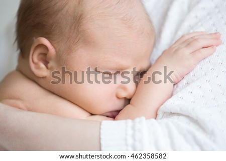Close-up portrait of funny newborn babe napping in mom arms. Adorable new born child sleeping on mom hands. Healthy little kid asleep. Love, bonding, happy family concept.