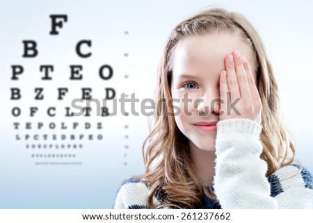 Close up portrait of girl reviewing eyesight closing eye with hand.Out of focus test chart in background. - stock photo