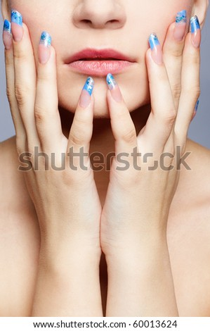 close-up portrait of girl's lower part of face and manicured fingers - stock photo
