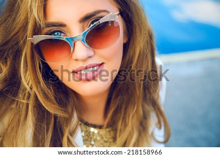 Close up portrait of gorgeous woman with big blue eyes perfect skin full lips and white teeth, posing near deep blue sea,smiling and looking on camera,wearing trendy vintage golden cat eye sunglasses. - stock photo