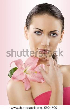 close up portrait of graceful brunette with pink lily and stunning blue eyes