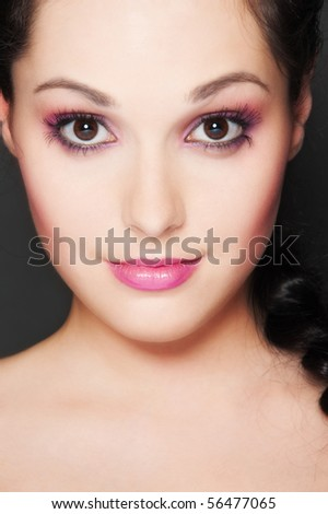 close-up portrait of graceful woman over dark background - stock photo
