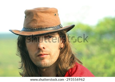 Close-up portrait of guy with long hair in cowboy hat. Style safari. Romance. Country style. - stock photo