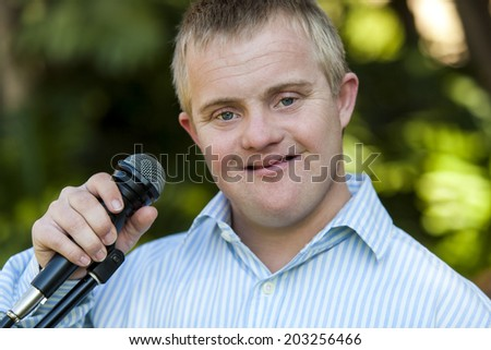Close up portrait of handicapped boy holding microphone outdoors - stock photo