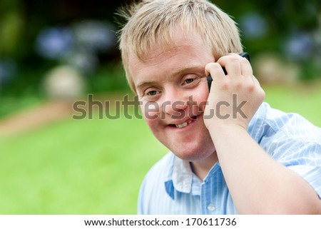 Close up portrait of handicapped boy talking on smart phone outdoors. - stock photo