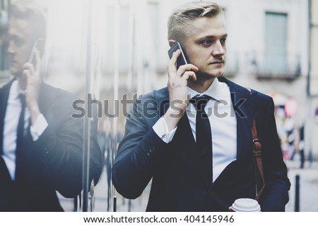 Close-up portrait of handsome bearded businessman wearing modern suit and talking on the smartphone while going to work on the urban street with coffee cup at morning - stock photo
