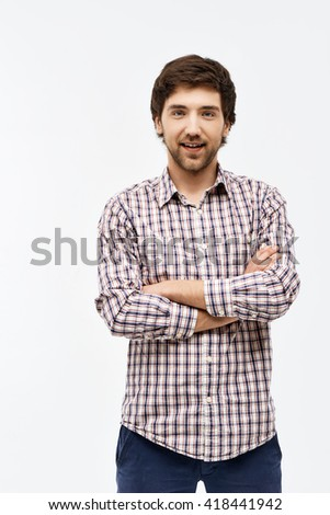 Close-up portrait of handsome confident young blue-eyed dark-haired man with arms crossed on chest wearing casual plaid shirt and jeans looking at camera. Isolated on white background. - stock photo