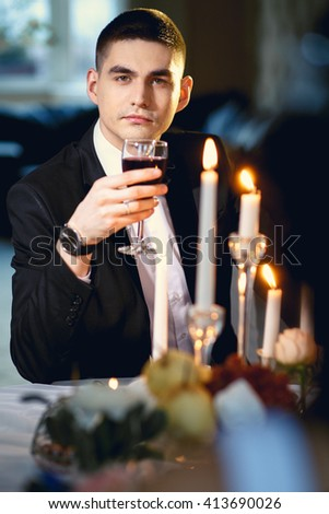 Close-up portrait of handsome groom, sitting by a table with decor and candles
