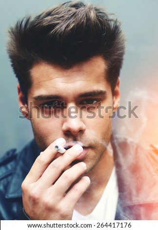 Close up portrait of handsome man exhaling cigarette smoke while looking to the camera, trendy attractive man blowing smoke out of mouth standing on grey background, filtered image, red flare light - stock photo