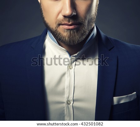 Close-up portrait of handsome stylish caucasian bearded young man in elegant blue suit and white shirt. Toned - stock photo