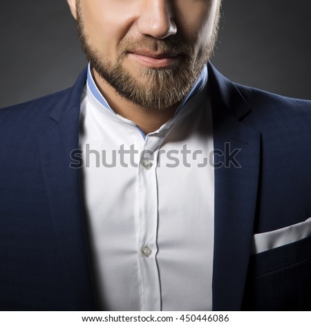 Close-up portrait of handsome stylish caucasian bearded young man in elegant blue suit and white shirt with perfect hair style smiling when looking at camera.  - stock photo
