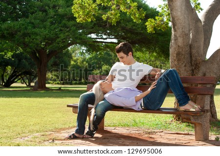 Close up portrait of handsome young couple relaxing on wooden bench in park. - stock photo