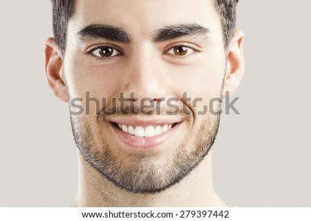 Close-up portrait of handsome young man,  isolated over a gray background - stock photo