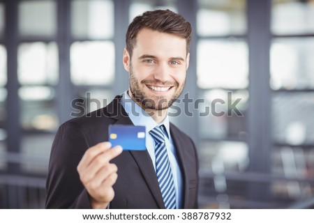 Close-up portrait of happy businessman showing credit card - stock photo