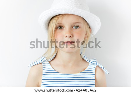 Close up portrait of happy Caucasian little female model looking and smiling at the camera with dreamy and thoughtful expression. Beautiful blonde preschool girl wearing fashionable clothes