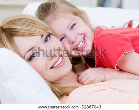 Close-up portrait of happy cheerful beautiful young mother with her little smiling daughter - indoors - stock photo