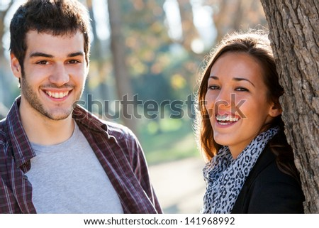 Close up portrait of happy couple laughing together in park. - stock photo