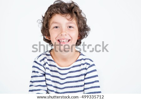 Close up portrait of happy cute little boy with curly hair smiling at camera over white background.