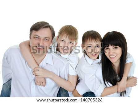 close-up portrait of happy family of four hugging on white background